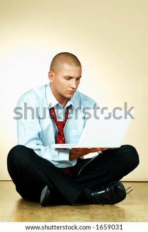 A businessman using laptop computer and sitting on wooden floor