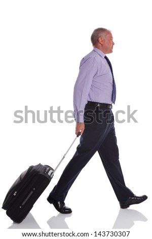 A businessman walking along pulling a suitcase, isolated on white background.