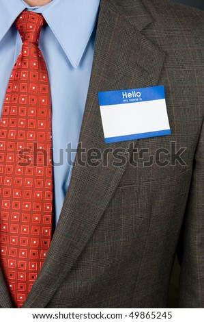 A businessman wearing a blank name tag and a sharp business suit. - stock photo