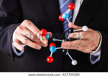 a businessman wearing a suit and a tie holding a trinitrotoluene tnt molecular model