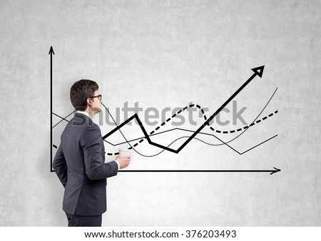 A businessman with a paper cup looking at graphs drawn on a concrete wall. Side view. Concrete background. Concept of defining a trend.