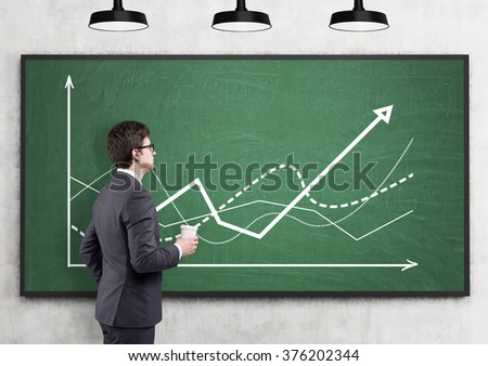 A businessman with a paper cup looking at graphs drawn on the green blackboard, three lamps above. Side view. Concrete background. Concept of defining a trend.