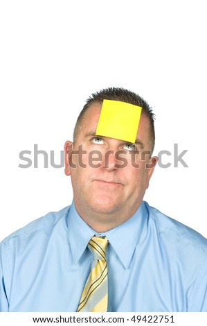 A businessman with a sticky note on his forehead. - stock photo