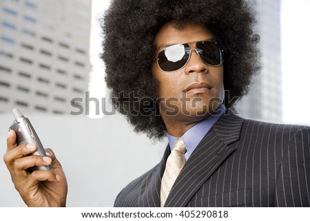 A businessman with an Afro hairstyle talking on a mobile phone - stock photo