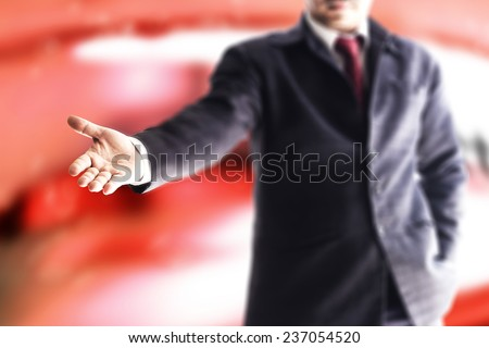 A businessman with an open hand ready to seal a deal over red tone office.