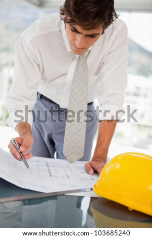 A businessman with blueprints of a building - stock photo