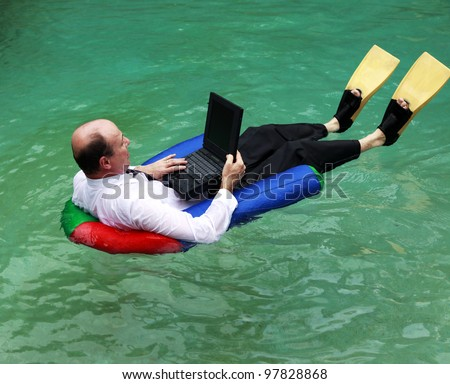 A businessman working from home dressed in business attire floating in a swimming pool on his laptop and wearing yellow flippers. - stock photo