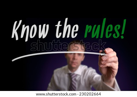 A businessman writing Know The Rules on a screen. Business Concept.