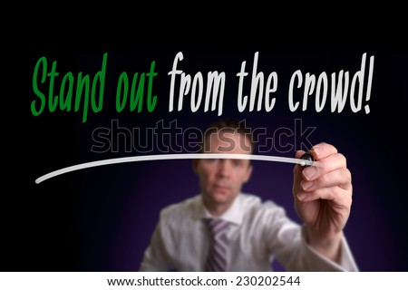 A businessman writing Stand Out From The Crowd on a screen. Business Concept. - stock photo