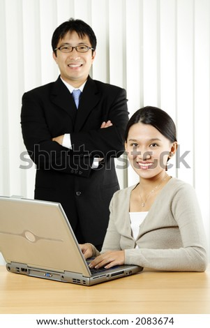 A businesswoman and a businessman in an office