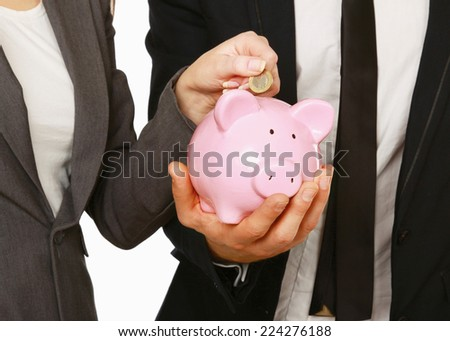 A businesswoman and man putting a coin into a piggy bank isolated on white background.