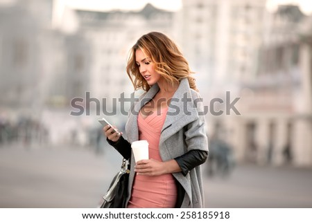 A businesswoman checking email via mobile phone and holding a coffee cup against urban scene. - stock photo