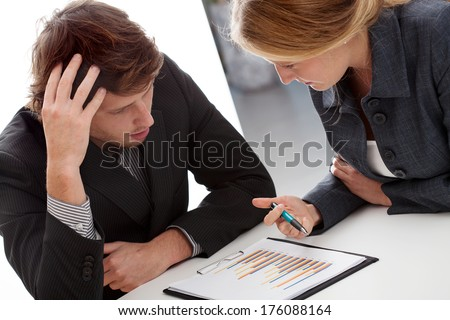 A businesswoman explaining her employee how to solve the problem - stock photo