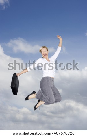 A businesswoman holding a briefcase, leaping in the air