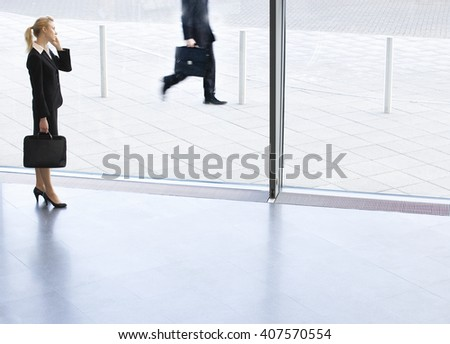 A businesswoman holding a mobile phone and briefcase - stock photo