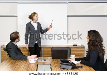 A businesswoman holding a presentation for two of her colleagues - stock photo