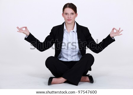 A businesswoman in a lotus position. - stock photo