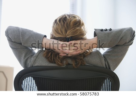 A businesswoman is seated in an office chair with her hands behind he head.  She is looking away from the camera.  Horizontal shot.