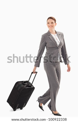 A businesswoman is smiling and walking with a suitcase