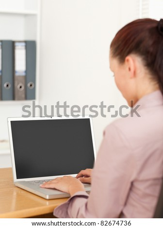 A businesswoman is typing on her laptop