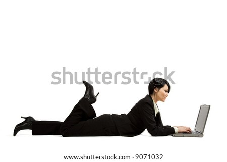 A businesswoman lying down on the floor typing on her laptop - stock photo