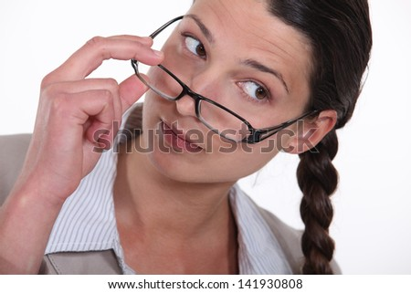 A businesswoman taking her glasses off.