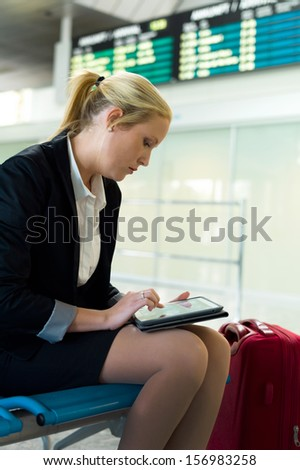 a businesswoman using her tablet computer at an airport. mobility and communication in business. roaming charges when abroad.