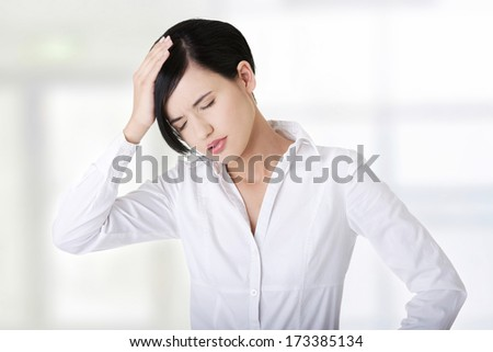 A businesswoman with a headache holding head