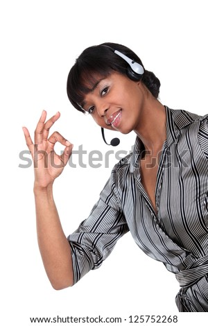 A businesswoman with a headset on making an ok sign. - stock photo