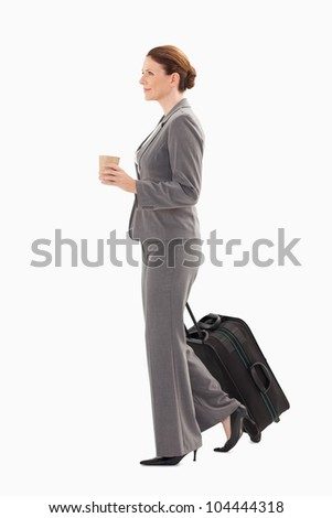 A businesswoman with a suitcase is holding coffee - stock photo