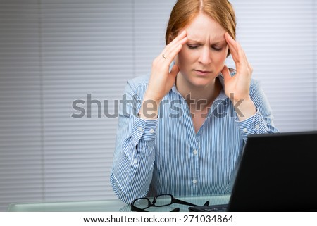 A businesswoman with migraine pains rubs the side of her head while at work.