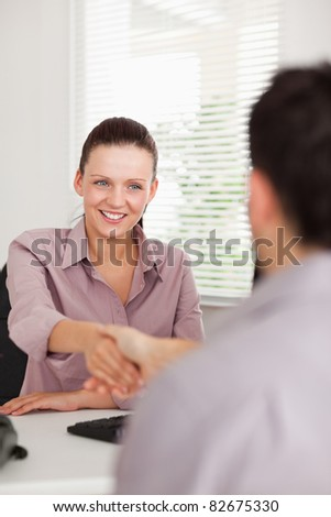 A busineswoman is shaking hands with a man