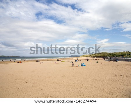 A busy beach in northern ireland with blue skies over head