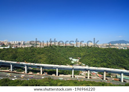A busy highway running near a green area in a large urban city. - stock photo