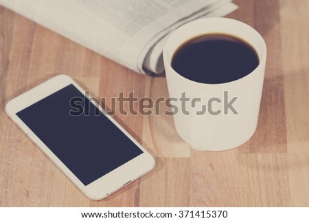 A busy morning. An image of a coffee cup with a mobile phone and a newspaper on a wooden table. Image has a vintage effect applied. - stock photo