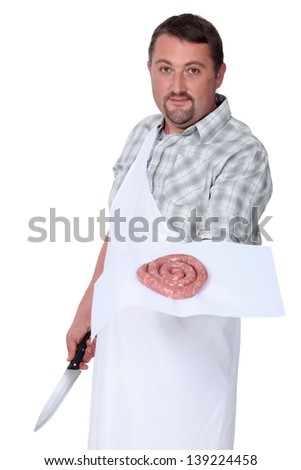 A butcher displaying a coil of sausage