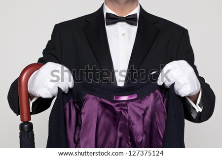 A butler holding a wool coat and umbrella ready to put on. - stock photo