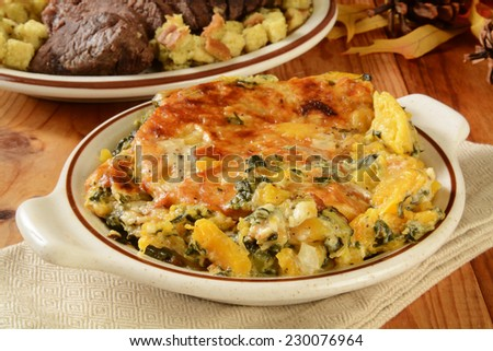 A butternut squash and spinach gratin casserole on a holiday table with roast beef in the background - stock photo