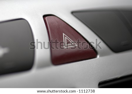 A button on a modern car dashboard to activate hazard lights - stock photo