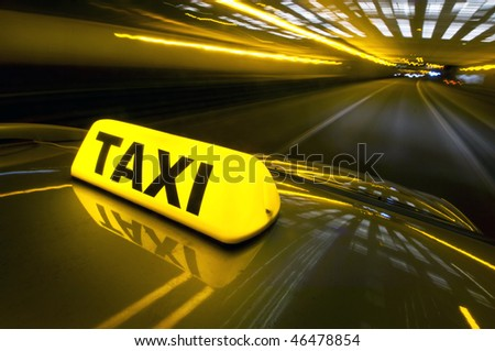 A cab at high speed on a motorway in an urban area with the lit taxi sign on top of its roof - stock photo