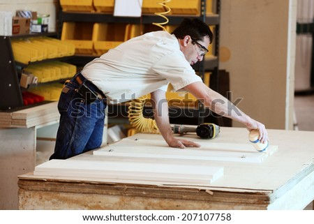 A cabinet maker glues and assembles the carcass of a cabinet - stock photo