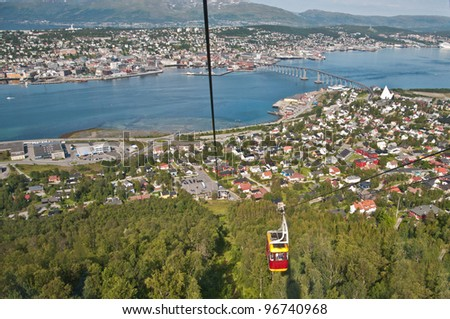 A cable car going up with Tromso panorama in the background. - stock photo