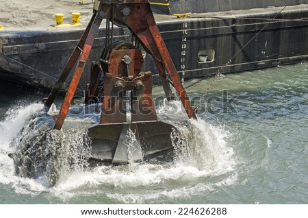A cable powered crane uses a clam shell bucket to remove sand in a dredging operation in Port Orford Oregon - stock photo