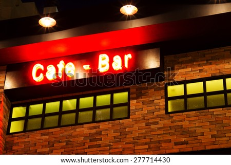 A cafe bar label with red neon, focus on brick - stock photo