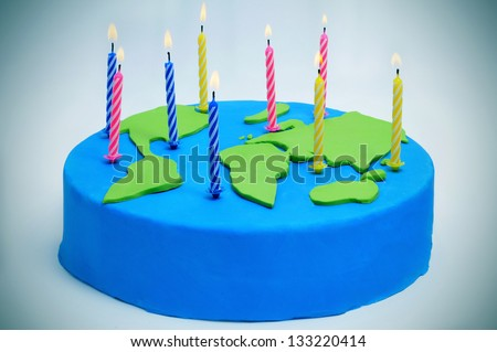 a cake decorated as a world map with candles for the International Mother Earth Day - stock photo