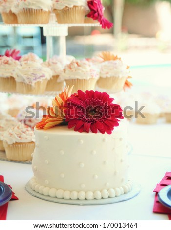 a cake with cupcakes in the background at a wedding party celebration - stock photo