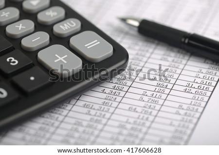 A calculator and a ball pen is on a balance sheet. Concept for sales, profit and cost.