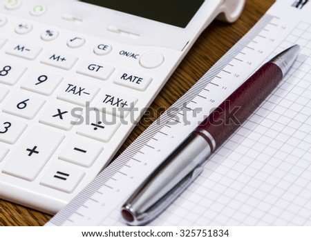 A calculator and a pen on desk for calculating taxes