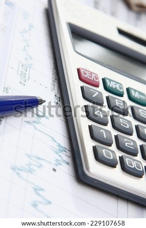A calculator and a pen over papers - stock photo