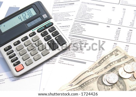 A calculator, dollars and pen on top of financial documents.